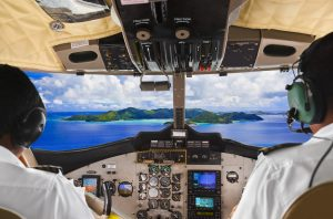 Pilots in the plane cockpit and tropical island